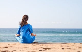 A nurse practicing self care, meditating on the beach after a hard day