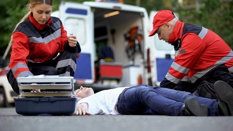 Medics helping man on road, preparing insulin to unconscious diabetic, first aid